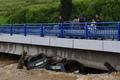 Na snímke ľudia sa pozerajú na autá zakliesnené pod mostom v rozvodnenom potoku v obci Jurské okr. Kežmarok 16. mája 2014 (foto: TASR)